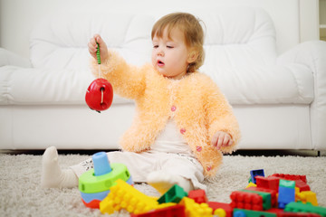 Pretty little girl sits on carpet and holds toy apple