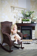 Little girl in white dress sits in wicker rocking chair