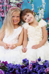 Two pretty little girls in white dresses sit among flowers