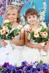 Two pretty little girls in white dresses hold bouquets of roses