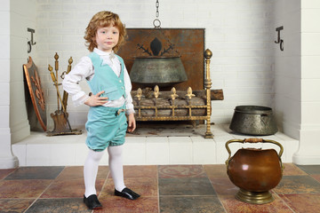 Little boy in medieval costume stands near fireplace