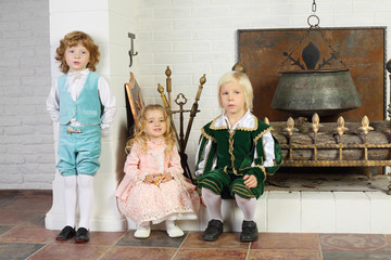 Two boys and girl in medieval costumes are near fireplace