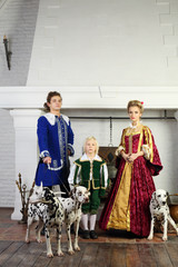Father, mother and son in bright medieval costume stand