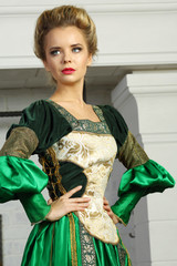 Beautiful young woman in luxury green medieval costume looks