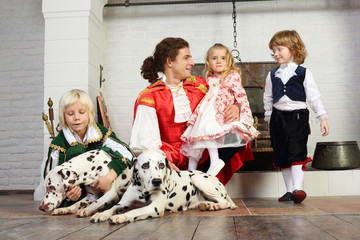 Father in medieval costume with three children and three dogs