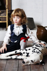 Serious pretty little boy in medieval costume sits