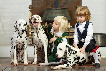 Two little boys in medieval costumes sit with three dalmatians