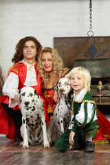 Happy father, mother and son in medieval costumes sit