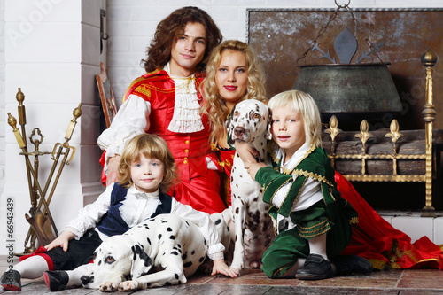 Happy father, mother and two sons in medieval costumes sit