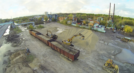 Excavators loaded sand into railway carriages.