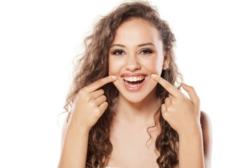 smiling girl holding the edges of her lips with her fingers