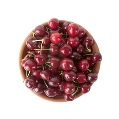 Red cherries in clay bowl isolated on white