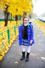 Kid girl in the uniform and coat has fun after school