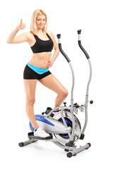 Woman giving a thumb up on a cross trainer machine