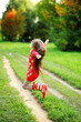Kid girl in red sweater and stripe rainboots having fun outdoors