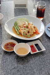 green papaya salad in white dish.