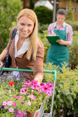 Woman put flowers in shopping cart greenhouse