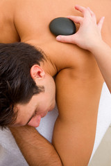 Therapist placing hot stone man's back
