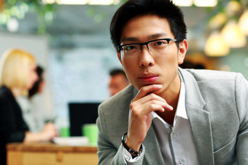 Portrait of a thoughtful asian man sitting in office