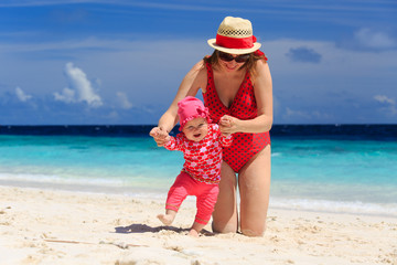 mother walking with little daughter on the beach