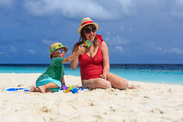 mother and son making soap bubbles on the beach