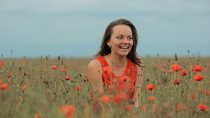 Beautiful smiling happy young girl sitting in poppy field