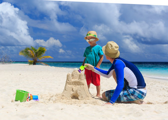 father and son building castle on the beach
