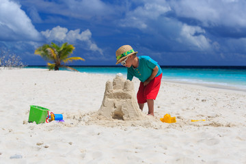 child building sand castle on tropical beach