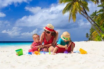 mother and kids playing on tropical beach