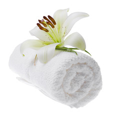 Rolled up towel with white lily, isolated