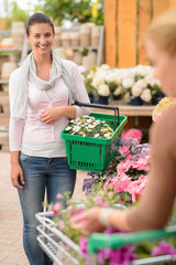 Woman buying flower shopping basket garden center