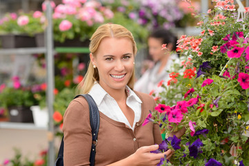Smiling customer with colorful flowers garden center