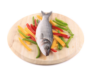 Fresh seabass fish on wooden platter.