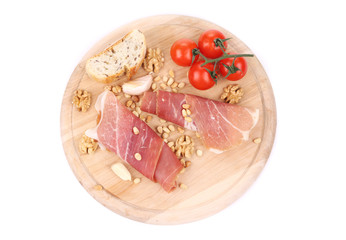 Prosciutto with tomatoes on wooden platter.
