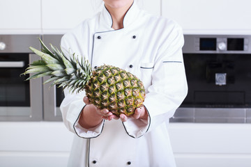 Closeup on pineapple in hand of housewife
