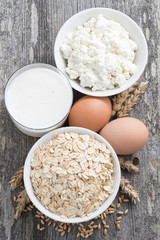 fresh products-oatmeal, eggs, cottage cheese and milk, top view