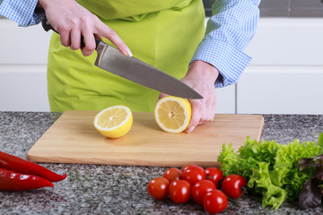 Housewife cut lemon on a wooden board