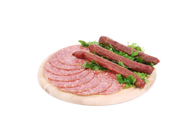 Composition of sausages on wooden platter.