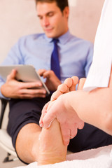 Therapist massaging businessman's foot