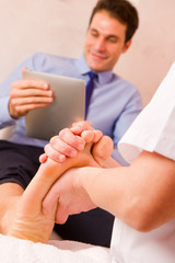 Masseuse massaging businessman's foot