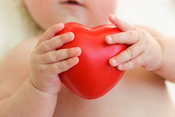 The child holding a red heart