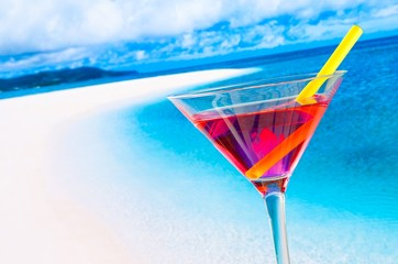 red cocktail on blur beach with space for text