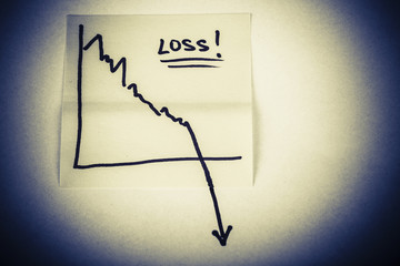 note paper with finance business graph going down - loss