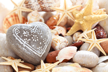 Heart shaped pebble against seashells background .