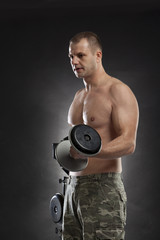 man lifting dumbbells hal naked on gray background