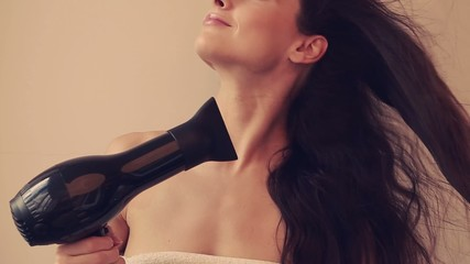 Beautiful woman drying healthy hair with natural emotion