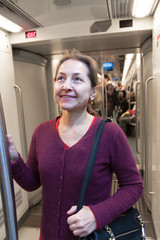 woman standing in  subway car.