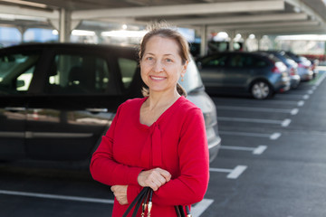 Smiling mature woman at parking