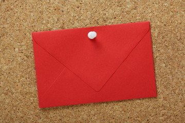 A sealed red envelope pinned to a cork notice board