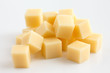 Cubes of yellow cheese stacked randomly on white. - 66957426